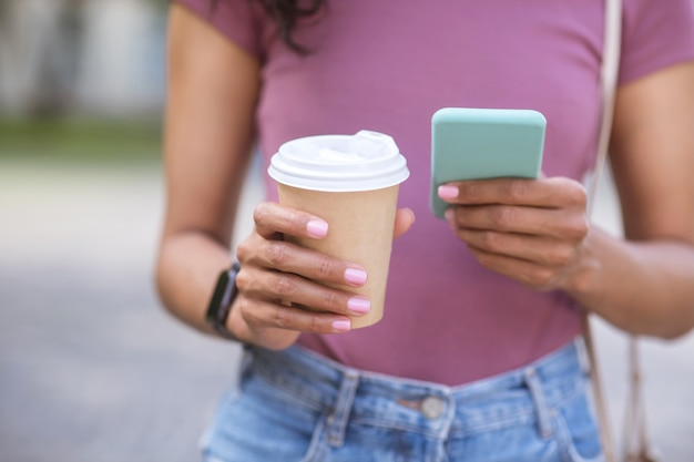 Photo. a girl making photo of a cup with coffee on a smartphone