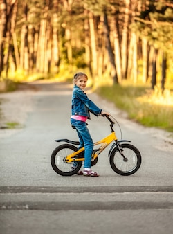 Photo of girl riding yellow bike at forest