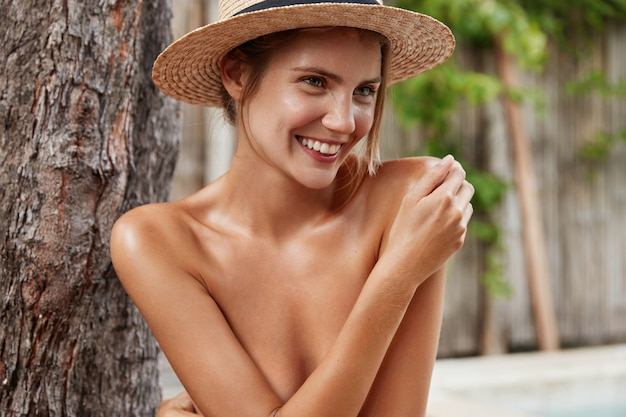 Photo of glad adorable young female model has bare perfect body, hides with hand, wears straw hat, has pleasant smile, demonstrates perfect healthy skin,