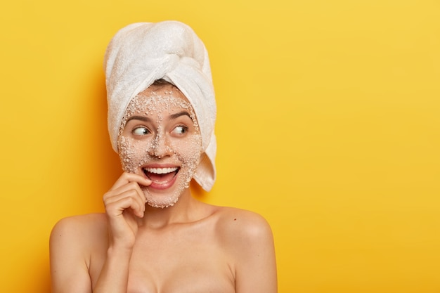 Photo of glad european girl with toothy smile, uses sea salt for spa procedures, takes shower, has smooth healthy skin, looks away, wears white towel, isolated over yellow background. beauty concept