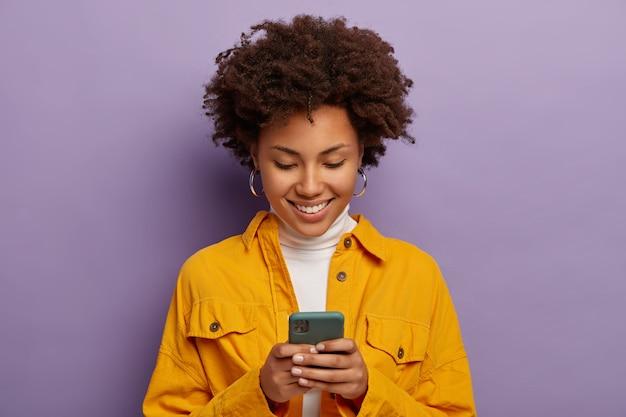 Foto di una donna felice, concentrata sullo smartphone, indossa una camicia gialla, sorride delicatamente, isolata sopra il muro viola dello studio