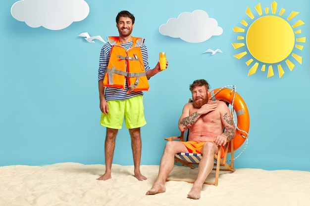 Photo of glad man suggests friend using sunscreen, has positive smile, wears lifejacket