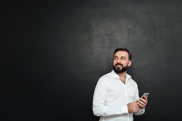 Photo of glad man in white shirt looking back while chatting or using wireless internetin on mobile phone over dark gray