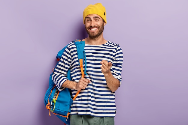 Photo of glad smiling man traveler points at you with index finger, carries rucksack, wears yellow hat and srtiped sweater, exprsses choice, picks up you, isolated on purple wall