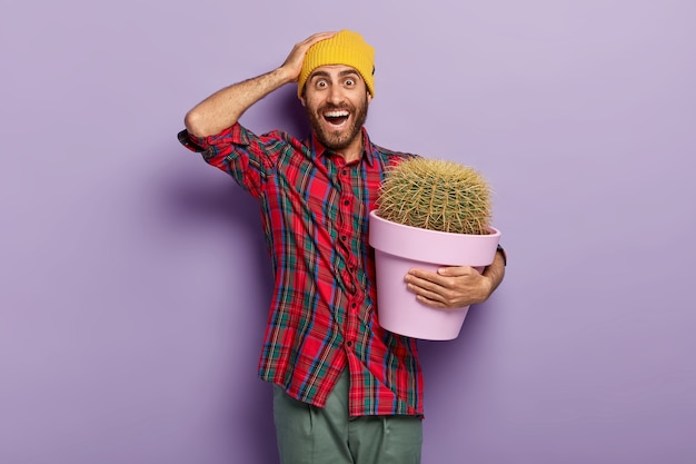 Photo of glad unshaven young man keeps hand on head, carries pot of green plant, receives cactus with prickly thorns as present, wears yellow hat and plait red shirt, cares about potted plant