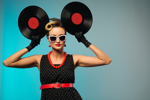 A photo of glamorous pin-up girl holding vinyl lp in hand -