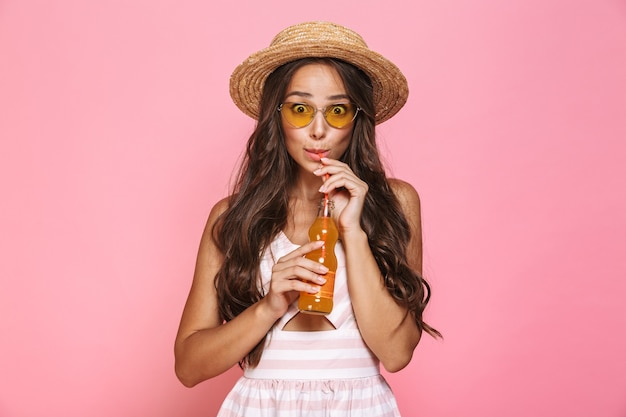 Photo of glamour woman 20s wearing sunglasses and straw hat drinking juice from glass bottle, isolated over pink wall