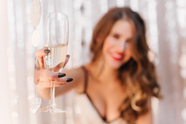 Foto del bicchiere di champagne sulla parete sfocata della ragazza riccia con labbra rosse che lo tengono.