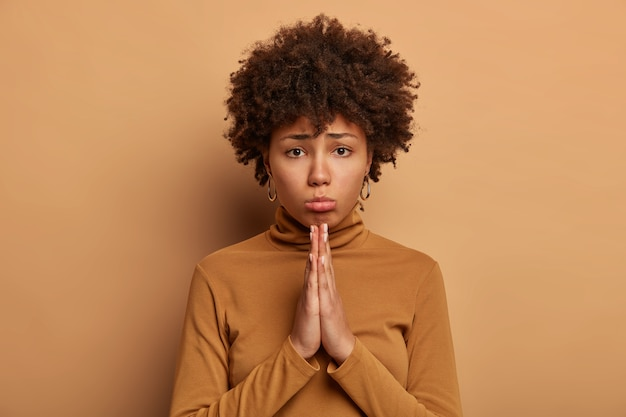 Photo of gloomy dark skinned curly woman asks for best, keeps palms pressed together, asks for forgiveness, dressed casually, isolated over brown wall, makes request. please do me favor