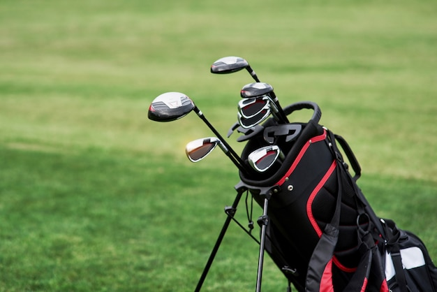 Photo of golf bag with sticks standing on the green lawn. close up view.