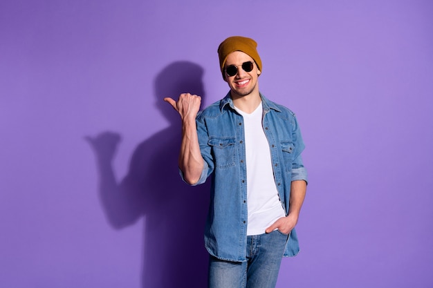 Photo of good cheerful attractive handsome freelancer holding hand in denim pocket cap smiling toothily pointing at empty space isolated over vivid purple color background