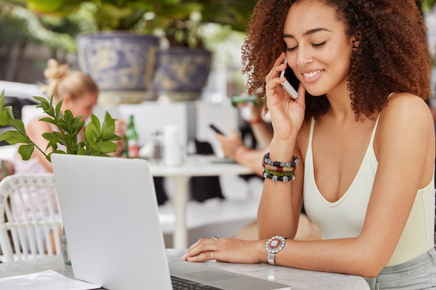 Photo of good looking african american female enterpreneur has work break in outdoor cafe, does remote work on laptop computer and makes call