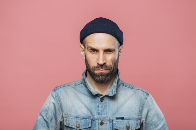 Photo of good looking bearded male blinks eye and looks seriously, wears denim jacket