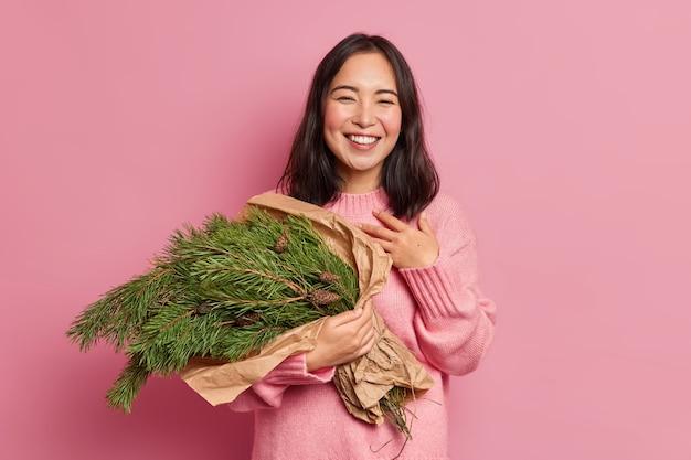 La foto della bella donna castana sorride ampiamente si sente soddisfatta tiene i rami degli abeti ha uno stato d'animo festoso che farà la composizione natalizia indossa il ponticello invernale
