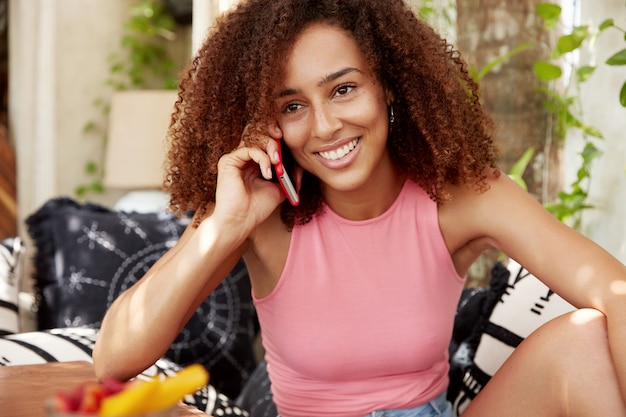 Photo of good looking cheerful african american woman enjoys pleasant conversation via cell phone, being in high spirit, feels relaxed as sits on comfortable sofa. communication and lifestyle