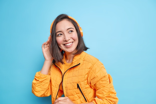 Photo of good looking teenage girl with eastern appearance listens music in modern headphones smiles broadly wears orange fashionable jacket isolated over blue wall. great playlist. music lover