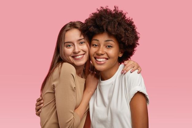 Foto di due giovani modelli di bell'aspetto che stanno vicini, si abbracciano e si divertono insieme, vestiti con abiti casual, modello su uno spazio rosa