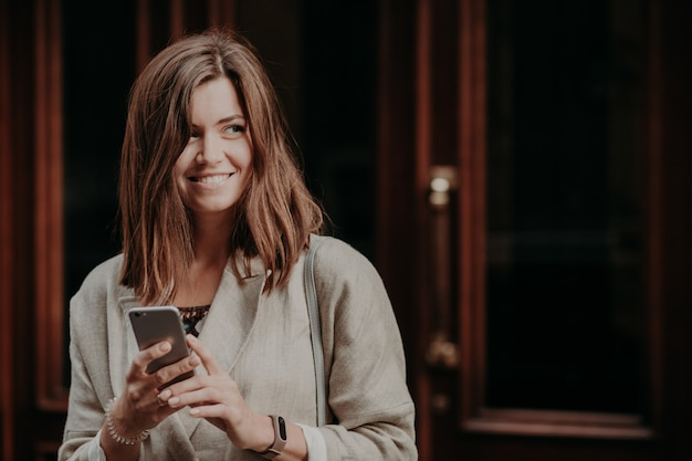 Photo of good looking woman searches information, uses cell phone, dressed in elegant jacket