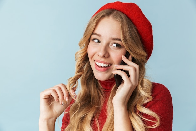 Photo of gorgeous girl 20s wearing red beret talking on cell phone isolated