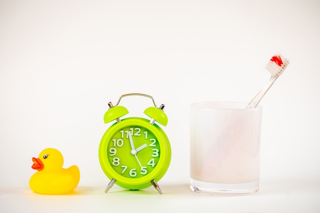 A photo of the green alarm clock and toothbrush.
