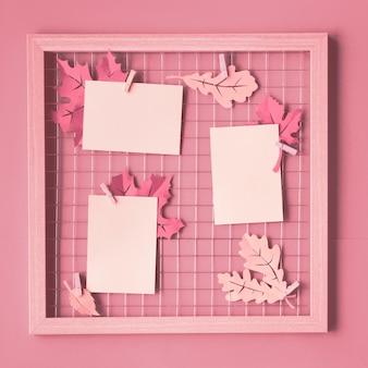 秋の紙の葉とペグに空白の紙カードの写真グリッドボード。写真や書き込み、正方形の構成のためのピンクのモノクロのトレンディなモックアップ。