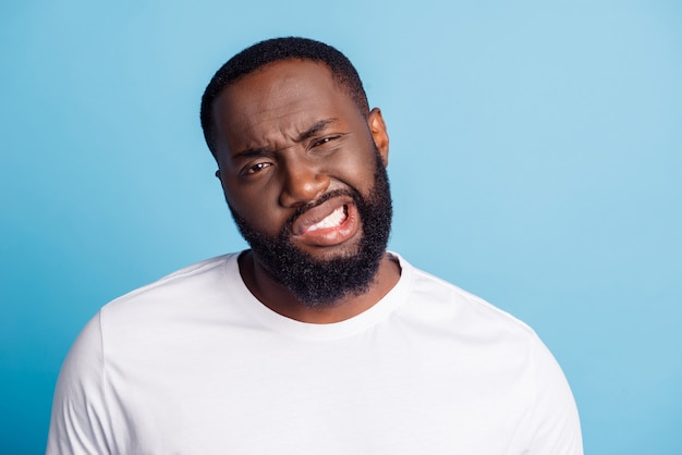 Photo of grimacing young man look camera wear white t-shirt over blue background