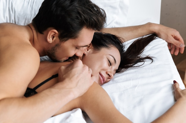 Photo of half-naked couple man and woman hugging together, while lying in bed at home or hotel apartment