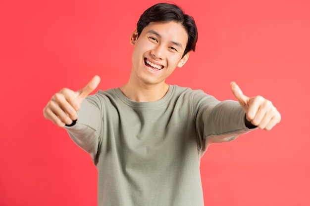 A photo of a handsome asian man holding up 2 thumbs with a cheerful face