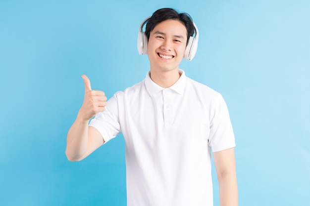 A photo of a handsome asian man listening to music and using his thumbs up