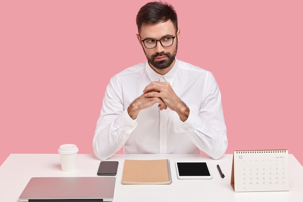 Photo of handsome bearded businessman has thoughtful expression, keeps hands together, dressed in formal wear, has everything on its places at desktop