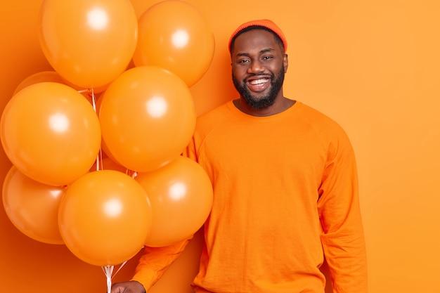 Photo of handsome bearded dark skinned man smiles joyfully