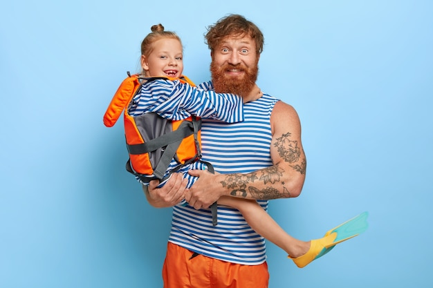 Photo of handsome bearded ginger man in casual wear, carries little beautiful girl in lifejacket, rubber fins, learns to swim with help of father