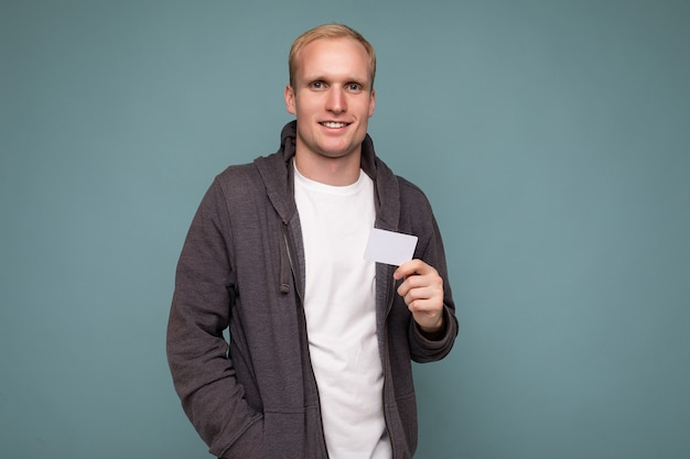 Photo of handsome blonde male person wearing grey sweater and white t-shirt isolated over blue background wall holding credit card looking at camera.