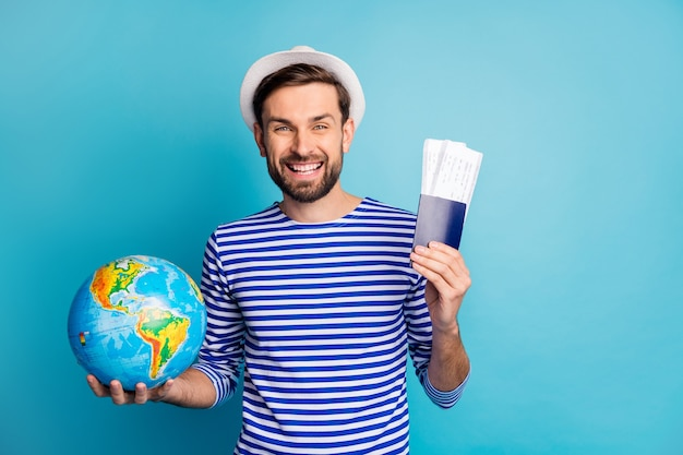 Photo of handsome cheerful guy hold world globe addicted traveler show tickets wait flight check-in wear striped sailor shirt vest frock panama isolated blue color
