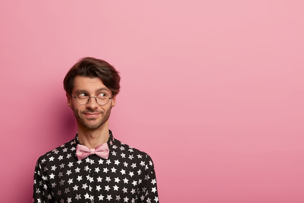 Photo of handsome cheerful man with trendy hairstyle, looks aside, wears optical glasses