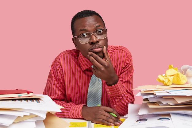 La foto del bel regista maschio dalla pelle scura indossa camicia e cravatta formali, tiene il mento, lavora alla relazione finanziaria alla scrivania, ha pile di documentazioni