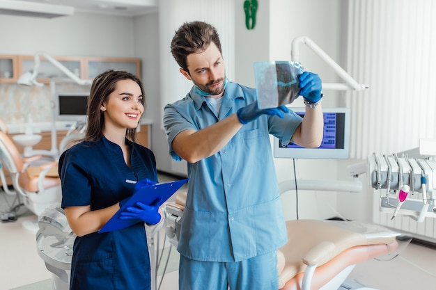 Photo of handsome dentist standing with her colleague and holding x-ray.