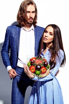 Photo of handsome elegant man in suit with beautiful woman in colorful dress with fresh bouquet