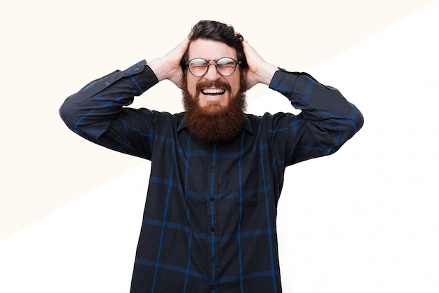 Photo of handsome frustrated bearded man with glasss, is putting hnads on head and closesd eyes