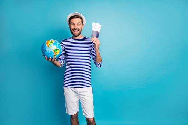 Photo of handsome funky guy hold world globe traveler prepare tickets wait flight check-in wear striped sailor shirt vest shorts panama isolated blue color