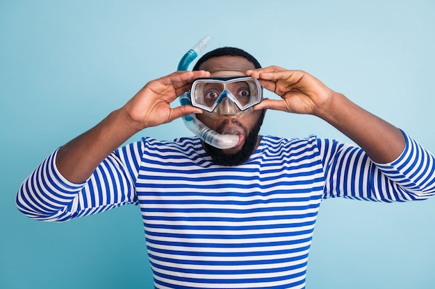 Photo of handsome funny dark skin guy tourist diving underwater mask see colorful fish corals breathing tube floating deep wear striped sailor shirt isolated blue color wall