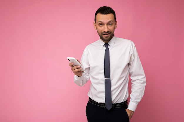 Photo of handsome good looking man wearing casual white shirt and tie isolated on pink background with empty space holding in hand and using mobile phone messaging sms looking at camera.