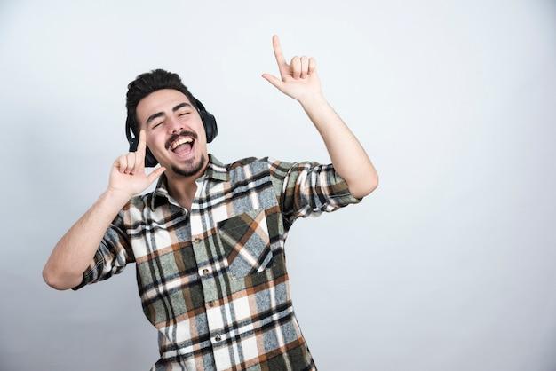 Foto del bel ragazzo in cuffie che ascolta una canzone sul muro bianco.