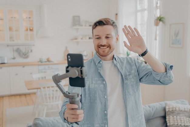 Photo of handsome guy in living room enjoying weekend, streaming live video on smartphone with gimbal stabilizer, showing new flat to his friends and waving with hand in hello gesture, casual dressed