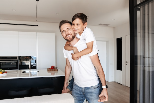 Photo of handsome happy man piggybacking his son, while resting in modern apartment