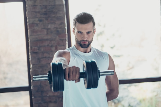 Photo of handsome hot beard guy morning training biceps muscles lift heavy dumbbell tempting eyes look sportswear tank-top training house big windows indoors