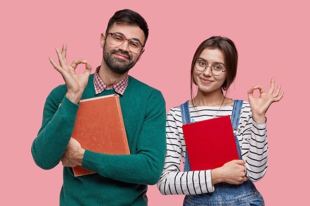 Photo of handsome male student and his female groupmate demonstrates okay gesture, agree with something