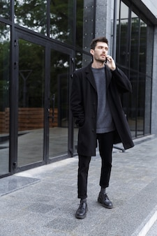 Photo of handsome man 20s talking on cell phone, while walking outdoor near glass building
