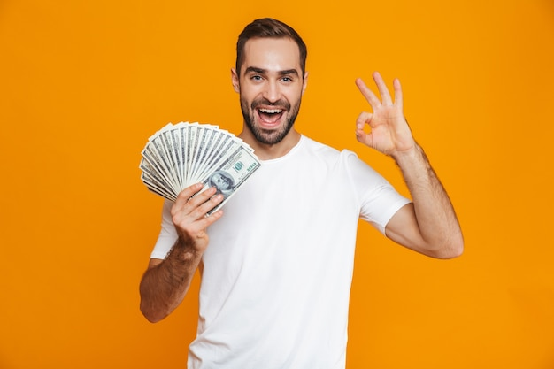 Photo of handsome man 30s in casual wear holding bunch of money, isolated