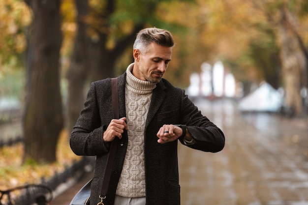Photo of handsome man 30s wearing warm clothes walking outdoor through autumn park, and looking at wrist watch